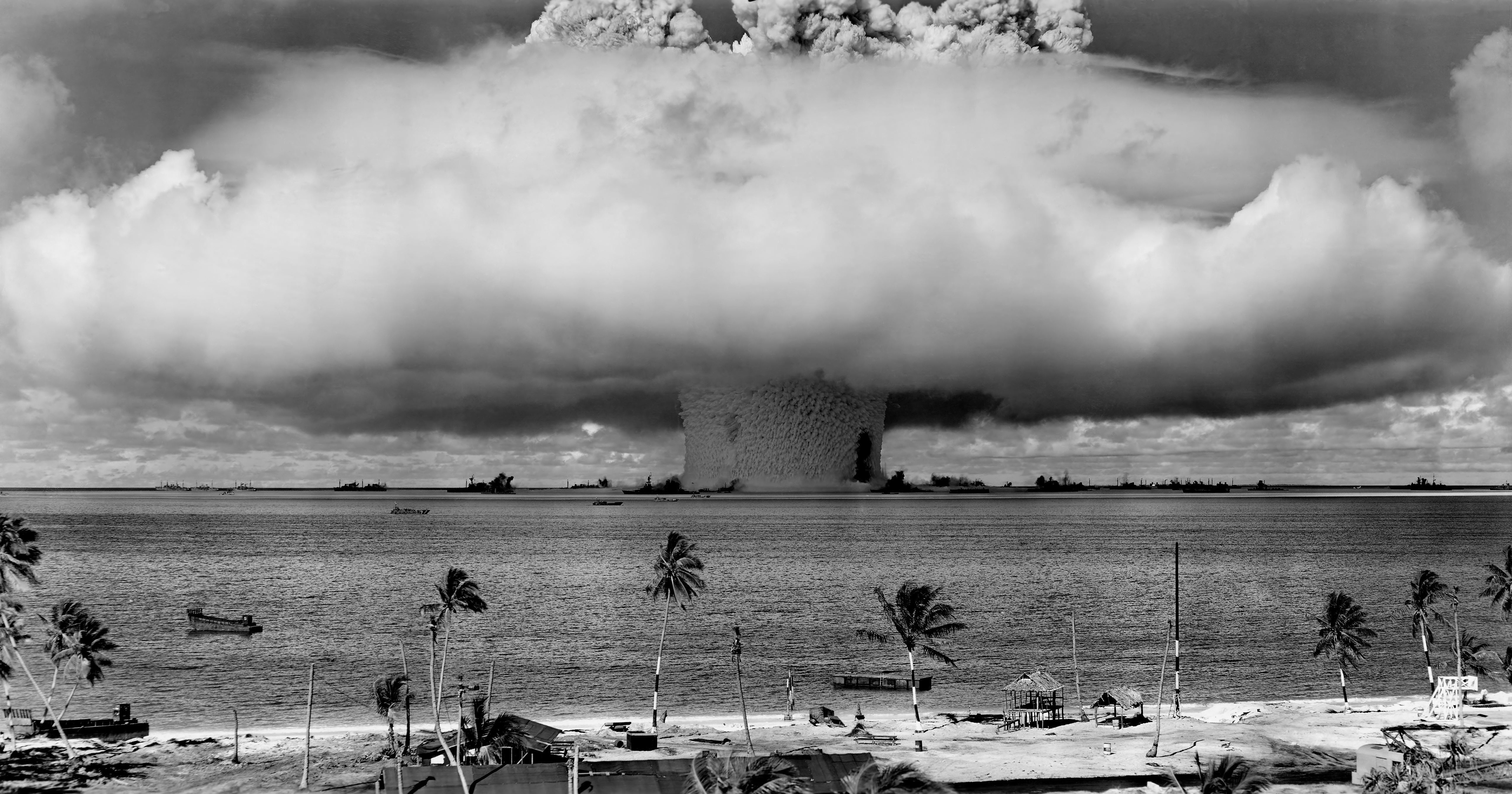 grayscale-photo-of-explosion-on-the-beach-73909-1
